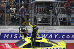 Ryan Blaney stands on his car after winning the NASCAR Cup Series auto race at Michigan International Speedway, Sunday, Aug. 22, 2021, in Brooklyn, Mich. (AP Photo/Carlos Osorio)
