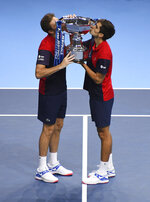 Pierre-Hugues Herbert of France, right, and Nicholas Mahut of France kiss trophy they have won after defeating Raven Klaasen of South Africa and Michael Venus of New Zealand following their ATP World Finals final doubles tennis match at the O2 arena in London, Sunday, Nov. 17, 2019. (AP Photo/Alberto Pezzali)