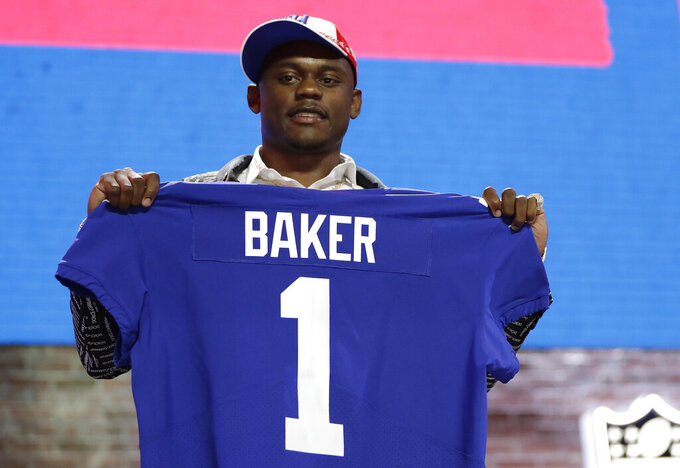 Georgia defensive back DeAndre Baker poses with his new jersey after the New York Giants selected Baker in the first round at the NFL football draft, Thursday, April 25, 2019, in Nashville, Tenn. (AP Photo/Mark Humphrey)
