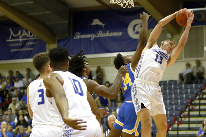 Chaminade guard Tyler Cartaino (13) grabs a rebound away from UCLA guard David Singleton (34) during the first half of an NCAA college basketball game Tuesday, Nov. 26, 2019, in Lahaina, Hawaii. (AP Photo/Marco Garcia)