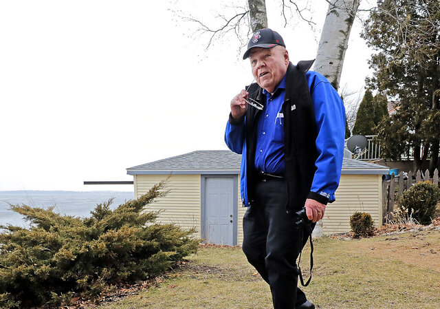 In this Thursday, March 12, 2020, Ed Hopkins, assistant climatologist with the Wisconsin State Climatology Office, approaches the shoreline of Lake Monona on the East Side of Madison, Wis. (John Hart/Wisconsin State Journal via AP)