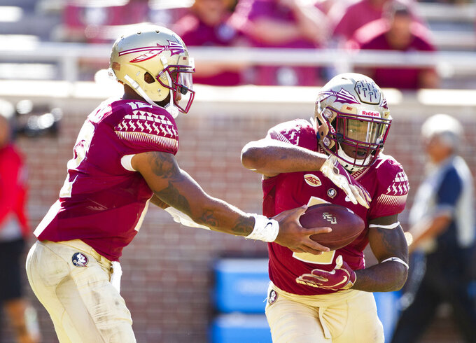 Florida State quarterback Deondre Francois hands the ball off to running back Cam Akers in the second half of an NCAA college football game in Tallahassee, Fla., Saturday, Oct.27, 2018. Clemson defeated Florida State 59-10. (AP Photo/Mark Wallheiser)