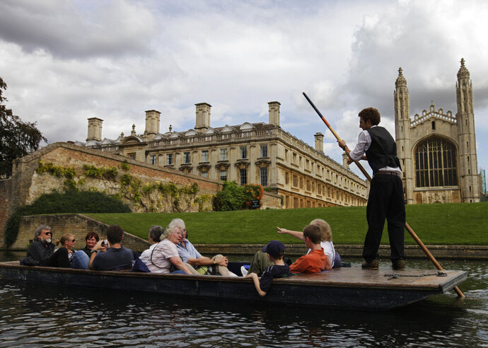 FILE - In this Tuesday Aug. 25, 2009 file photo, tourists enjoy a boat ride on the river Cam, in Cambridge, England. The University of Cambridge said Thursday Oct. 1, 2020, that it will kick all fossil fuel investments out of its portfolio within the next decade as part of a plan to end the emissions of greenhouse gases it's responsible for by 2038. (AP Photo/Lefteris Pitarakis, File)