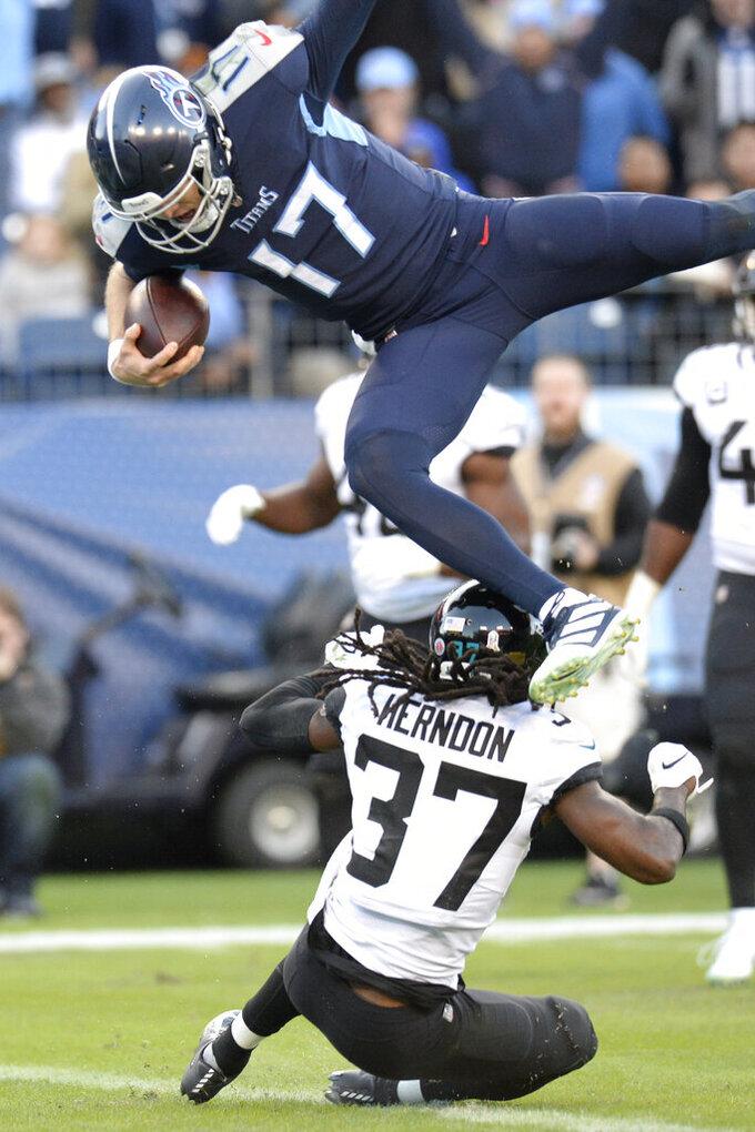 Tennessee Titans quarterback Ryan Tannehill (17) jumps over Jacksonville Jaguars cornerback Tre Herndon (37) as Tannehil scores a touchdown on a 21-yard run in the first half of an NFL football game Sunday, Nov. 24, 2019, in Nashville, Tenn. (AP Photo/Mark Zaleski)