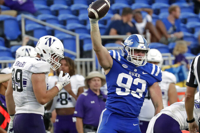 Duke defensive end Ben Frye (93) celebrates in front of Northwestern tight end Charlie Mangieri (89) after he recovered a fumble during the second half of an NCAA college football game in Durham, N.C., Saturday, Sept. 18, 2021. (AP Photo/Chris Seward)
