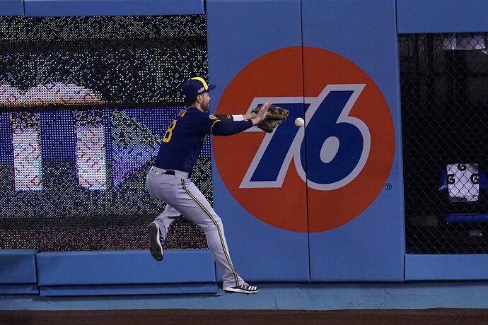 Milwaukee Brewers right fielder Ryan Braun leaps for but can't catch a line drive from Los Angeles Dodgers' Mookie Betts during the first inning in Game 1 of a National League wild-card baseball series Wednesday, Sept. 30, 2020, in Los Angeles. (AP Photo/Ashley Landis)