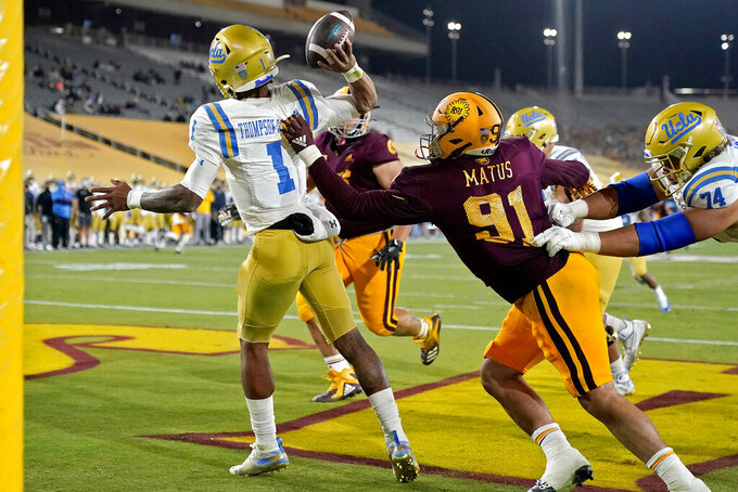 UCLA quarterback Dorian Thompson-Robinson (1) intentionally grounds the football in the end zone for a safety as Arizona State defensive end Michael Matus (91) defends during the second half of an NCAA college football game, Sunday, Dec. 6, 2020, in Tempe, Ariz. UCLA won 25-18. (AP Photo/Matt York)