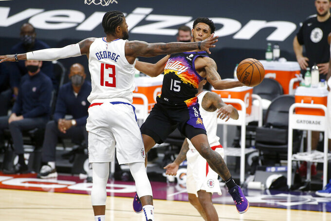 Phoenix Suns guard Cameron Payne (15) attempts to pass the ball around the defense of Los Angeles Clippers forward Paul George (13) during the second half of an NBA basketball game Sunday, Jan. 3, 2021, in Phoenix. (AP Photo/Ralph Freso)