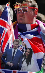 A royal fan waits to watch a rehearsal of the royal wedding in Windsor, England, Thursday, May 17, 2018. Preparations are being made in the town ahead of the wedding of Britain's Prince Harry and Meghan Markle that will take place in Windsor on Saturday May 19. (AP Photo/Frank Augstein)