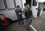 In this July 8, 2019, photo, a U.S. Immigration and Customs Enforcement (ICE) officers transfer a man in hand and ankle cuffs onto a van during an operation in Escondido, Calif. The carefully orchestrated arrest last week in this San Diego suburb illustrates how President Donald Trump's pledge to start deporting millions of people in the country illegally is virtually impossible with ICE's budget and its method of picking people up. (AP Photo/Gregory Bull)