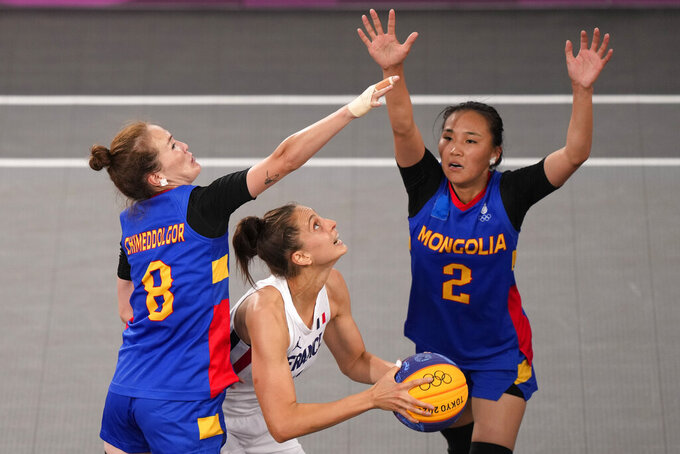 Ana Maria Filip, center, of France, looks for a shot under pressure from Chimeddolgor Enkhtaivan (8) and Tserenlkham Munkhsaikhan (2), of Mongolia, during a women's 3-on-3 basketball game at the 2020 Summer Olympics, Monday, July 26, 2021, in Tokyo, Japan. (AP Photo/Charlie Riedel)