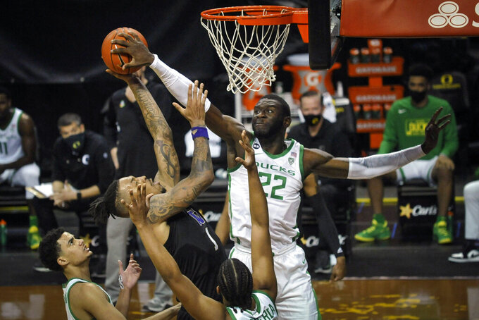 Washington forward Nate Roberts (1) has his shot blocked by Oregon center Franck Kepnang (22) as Oregon guards Will Richardson (0) and LJ Figueroa (12) watch the play during the first half of an NCAA college basketball game Saturday, Feb. 6, 2021, in Eugene, Ore. (AP Photo/Andy Nelson)