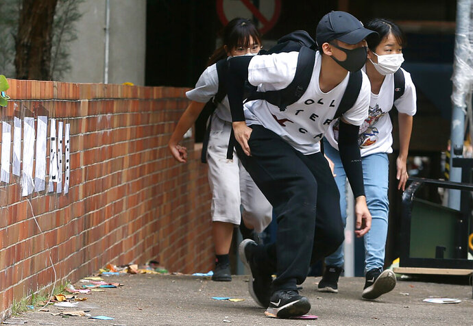 People wearing face masks duck down as they walk at Hong Kong Polytechnic University in Hong Kong, Tuesday, Nov. 19, 2019. About 100 anti-government protesters remained holed up at a Hong Kong university Tuesday as a police siege of the campus entered its third day. (AP Photo/Achmad Ibrahim)