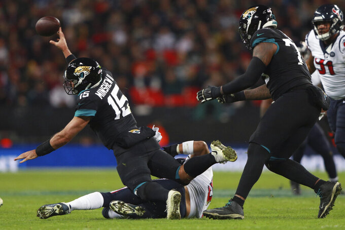 Houston Texans outside linebacker Brennan Scarlett (57) hits Jacksonville Jaguars quarterback Gardner Minshew (15) during the second half of an NFL football game at Wembley Stadium, Sunday, Nov. 3, 2019, in London. (AP Photo/Ian Walton)