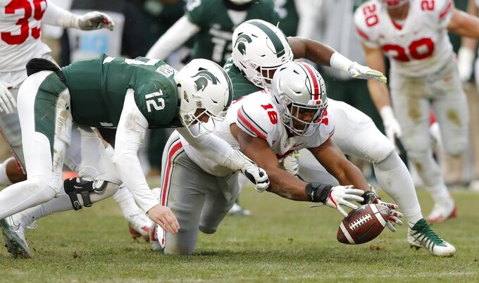 Ohio State defensive end Jonathon Cooper (18) recovers a fumble by Michigan State quarterback Rocky Lombardi (12) during the second half of an NCAA college football game, Saturday, Nov. 10, 2018, in East Lansing, Mich. (AP Photo/Carlos Osorio)