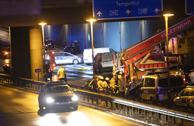 Forensic experts are investigating a car at the city motorway A100 after an accident in Berlin, Germany, Tuesday, Aug. 18, 2020. According to German news agency dpa, prosecutors say the series of crashes caused by a 30-year-old Iraqi man on the highway was an Islamic extremist attack. (Paul Zinken/dpa via AP)