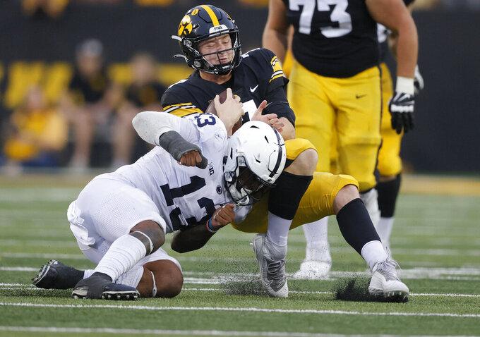 Penn State linebacker Ellis Brooks (13) tackles Iowa quarterback Spencer Petras (7) during the second half of an NCAA college football game, Saturday, Oct. 9, 2021, in Iowa City, Iowa. Iowa won 23-20. (AP Photo/Matthew Putney)