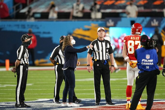 A health care worker tosses the coin before the NFL Super Bowl 55 football game between the Tampa Bay Buccaneers and the Kansas City Chiefs, Sunday, Feb. 7, 2021, in Tampa, Fla. (AP Photo/David J. Phillip)