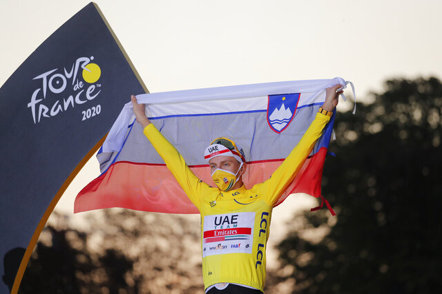 Tour de France winner Slovenia's Tadej Pogacar, wearing the overall leader's yellow jersey, celebrates on the podium with the Slovenian flag after the twenty-first and last stage of the Tour de France cycling race over 122 kilometers (75.8 miles), from Mantes-la-Jolie to Paris, France, Sunday, Sept. 20, 2020. (AP Photo/Christophe Ena)