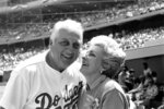 FILE - Jo Lasorda, wife of Los Angeles Dodgers' manager Tommy Lasorda, leans up to give him a good luck kiss on the start of his 35th season with the Dodger organization, in Los Angeles in this April 4, 1984, file photo. Jo Lasorda has died. She was 91. She died Monday night, Sept. 20, 2021, at her home in Fullerton, the team said Tuesday. No cause of death was given. (AP Photo/Lennox Mclendon, File)