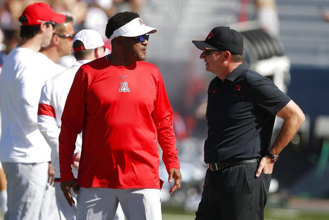 Arizona head coach Kevin Sumlin, left, and Oregon State head coach Jonathan Smith talk before an NCAA college football game, Saturday, Nov. 2, 2019, in Tucson, Ariz. (AP Photo/Rick Scuteri)