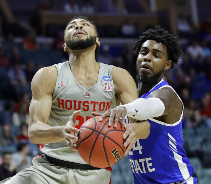 Georgia State's Devin Mitchell (24) tries to steal the ball from Houston's Galen Robinson Jr. during the first half of a first round men's college basketball game in the NCAA Tournament Friday, March 22, 2019, in Tulsa, Okla. (AP Photo/Charlie Riedel)