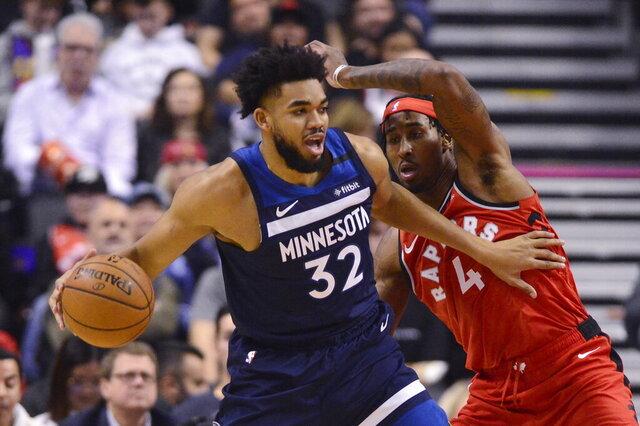 Minnesota Timberwolves centre Karl-Anthony Towns (32) drives past Toronto Raptors forward Rondae Hollis-Jefferson (4) during first half NBA basketball action in Toronto, Monday, Feb. 10, 2020. (Frank Gunn/The Canadian Press via AP)