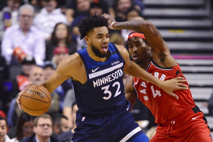 Minnesota Timberwolves centre Karl-Anthony Towns (32) drives past Toronto Raptors forward Rondae Hollis-Jefferson (4) during first half NBA basketball action in Toronto, Monday, Feb. 10, 2020. (Frank Gunn/The Canadian Press via AP)
