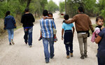 In this Thursday, March 14, 2019, photo, a group of migrant families walk from the Rio Grande, the river separating the U.S. and Mexico in Texas, near McAllen, Texas. The migrants said they crossed the river in an inflatable raft and were hoping to be apprehended by the Border Patrol so they could be processed and released. (AP Photo/Eric Gay)