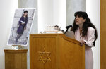 FILE - In this April 29, 2019, file photo, a photograph of Lori Kaye, who was killed when a gunman opened fire inside the Chabad of Poway synagogue, is displayed at left, during Kaye's funeral in Poway, Calif., as her daughter Hannah speaks at right. A Jewish civil rights group says at least a dozen white supremacists have been arrested on allegations of plotting, threatening or carrying out anti-Semitic attacks in the U.S. since the massacre at a Pittsburgh synagogue in 2018. The Anti-Defamation League's Center on Extremism's tally of the arrests includes the April 2019 capture of John T. Earnest, who is charged with killing one person and wounding three others in a shooting at the Poway synagogue. (AP Photo/Gregory Bull, File)