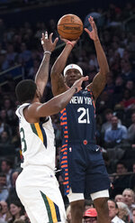 New York Knicks guard Damyean Dotson (21) shoots a 3-pointer past Utah Jazz forward Royce O'Neale (23) during the first half of an NBA basketball game Wednesday, March 20, 2019, at Madison Square Garden in New York. (AP Photo/Mary Altaffer)