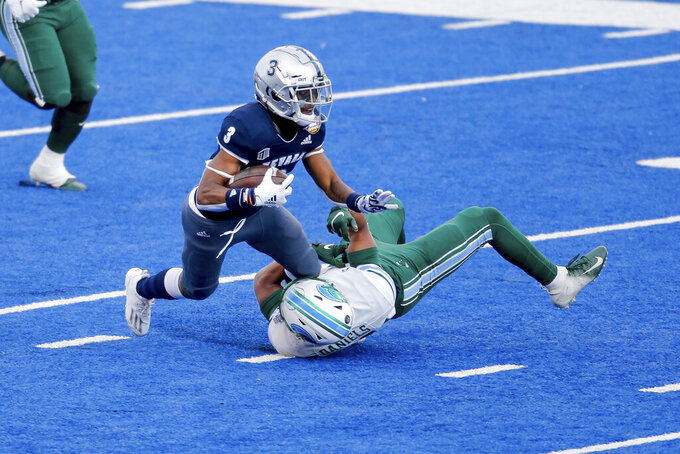 Nevada's Jamaal Bell (3) is tackled by Tulane's Christian Daniels (14) on a kick return during the second half of the Famous Idaho Potato Bowl NCAA college football game, Tuesday, Dec. 22, 2020, in Boise, Idaho. Nevada won 38-27. (AP Photo/Steve Conner)