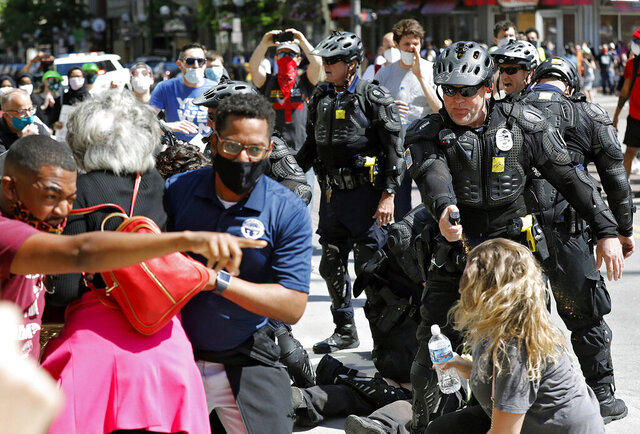 FILE - In this file photo from May 30, 2020, Congresswomen Joyce Beatty and Columbus City Council President Shannon Hardin try to intervene as Columbus Police use pepper spray on demonstrators during a protest on the death of George Floyd on South High Street near the Ohio Statehouse in Columbus, Ohio. Ohio is developing a statewide standard for police departments to follow when dealing with the types of protests over police brutality and racism that erupted in May and June after the killing of Floyd in Minneapolis. (Kyle Robertson/The Columbus Dispatch via AP, File)