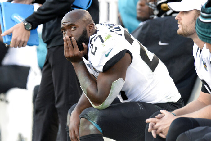 FILE - In this Nov. 24, 2019, file photo, Jacksonville Jaguars running back Leonard Fournette (27) sits on the bench in the first half of an NFL football game against the Tennessee Titans, in Nashville, Tenn. Fournette used to be considered a building block in Jacksonville. Then he ended up on the trading block. Now, the bruising running back is entering the final year of his rookie contract and facing an uncertain future with the franchise. (AP Photo/Mark Zaleski, File)