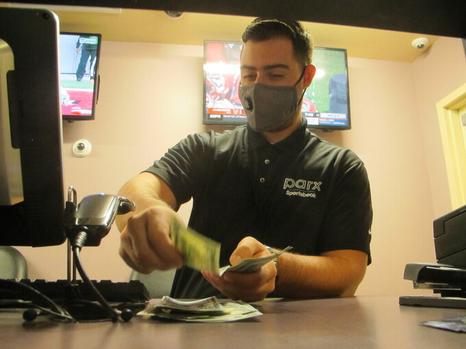 A clerk counts money at the sports betting lounge at Freehold Raceway in Freehold, N.J. on Oct. 24, 2020. A report released Feb. 2, 2021 by the American Gaming Association predicts fewer Americans will bet on this year's Super Bowl, a decrease driven largely by fewer people back at work in offices where betting pools are circulated. But the report also predicts a record amount will be wagered online this year. (AP Photo/Wayne Parry)