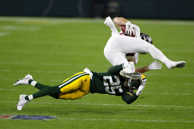 Green Bay Packers' Will Redmond (25) tackles Atlanta Falcons' Hayden Hurst, top, during the first half of an NFL football game, Monday, Oct. 5, 2020, in Green Bay, Wis. (AP Photo/Tom Lynn)