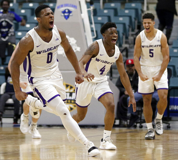 Abilene Christian guard Jaylen Franklin (0), guard Damien Daniels (4) and guard Payten Ricks (5) celebrate the team's lead in the final minute of an NCAA college basketball game against New Orleans for the Southland Conference men's tournament title Saturday, March 16, 2019, in Katy, Texas. (AP Photo/Michael Wyke)