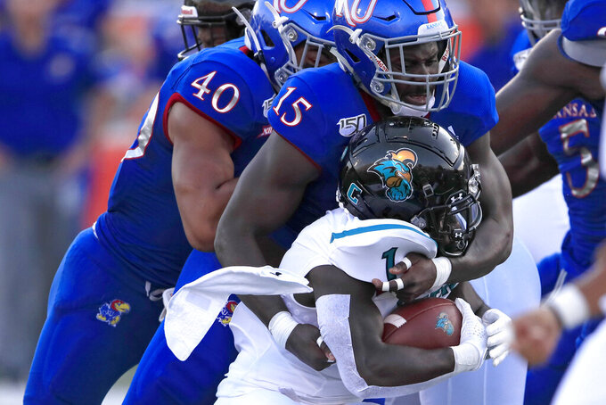 Coastal Carolina running back CJ Marable (1) is stopped by Kansas linebackers Kyron Johnson (15) and Dru Prox (40) during the first half of an NCAA college football game in Lawrence, Kan., Saturday, Sept. 7, 2019. (AP Photo/Orlin Wagner)