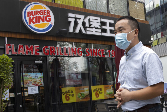 FILE - In this file photo taken Friday, July 17, 2020, a man wearing a mask to curb the spread of the coronavirus walks past a Burger King restaurant franchise in Beijing. The operator of six Burger King outlets in southern China has been required to pay more than $400,000 in fines and other penalties for using expired food, a regulator announced Tuesday, Aug 25, 2020. (AP Photo/Ng Han Guan, File)