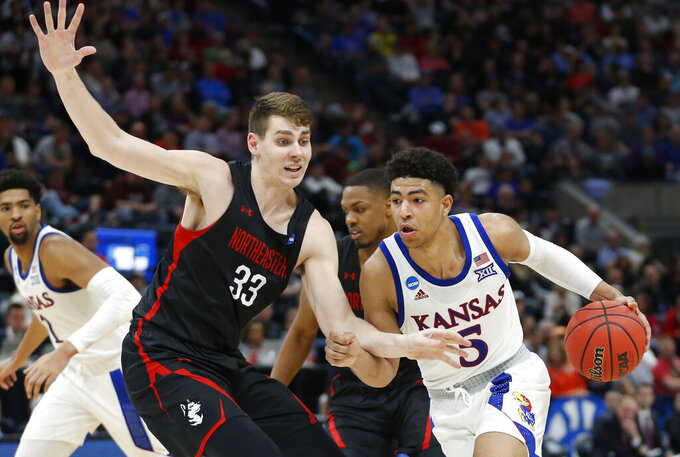 Kansas guard Quentin Grimes (5) drives around Northeastern forward Tomas Murphy (33) during the second half of a first-round game in the NCAA men's college basketball tournament Thursday, March 21, 2019, in Salt Lake City. (AP Photo/Rick Bowmer)