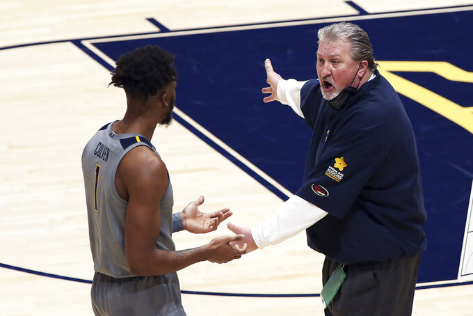 West Virginia coach Bob Huggins speaks with forward Derek Culver (1) during the first half of an NCAA college basketball game against Kansas, Saturday, Feb. 6, 2021, in Morgantown, W.Va. (AP Photo/Kathleen Batten)