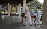 Sri Lankan municipal workers carry the coffin of a COVID-19 victim at a cemetery in Colombo, Sri Lanka, Friday, Jan. 22, 2021. Sri Lanka on Friday approved the Oxford-AstraZeneca vaccine for COVID-19 amid warnings from doctors that front-line health workers should be quickly inoculated to stop the system from collapsing. (AP Photo/Eranga Jayawardena)