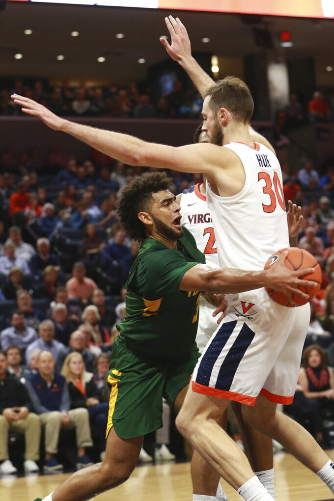 Vermont forward Anthony Lamb (3) tries to get the ball past Virginia forward Jay Huff (30) during the first half of an NCAA college basketball game Tuesday, Nov. 19, 2019, in Charlottesville, Va. (AP Photo/Steve Helber)