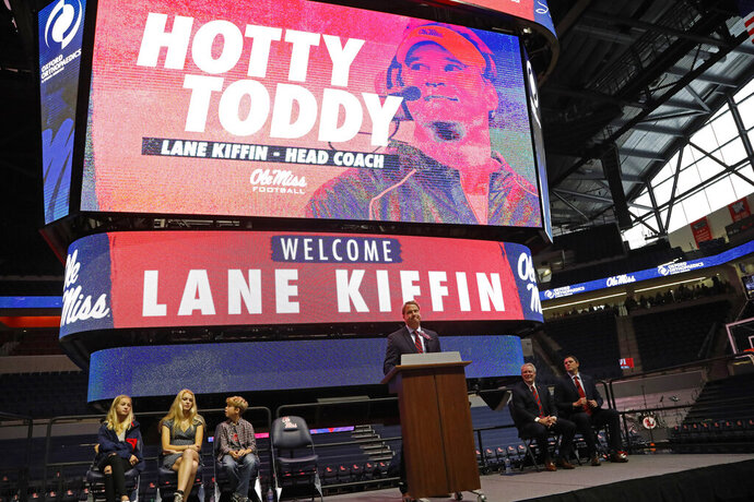 FILE - In this Monday, Dec. 9, 2019, file photo, Lane Kiffin speaks to Mississippi fans after being announced as the new head football coach during a introductory press conference in Oxford, Miss. In attendance were his children, daughters Presley Kiffin, 13, left, Landry Kiffin, 15, second from left, and son Knox Kiffin, 10. Mississippi State's Mike Leach and Mississippi's Lane Kiffin brought big names and offensive pedigrees to the Magnolia State. But they drew huge challenges for their debuts, with the Bulldogs visiting defending national champion and No. 6 LSU and the Rebels hosting No. 5 Florida. (AP Photo/Rogelio V. Solis, File)