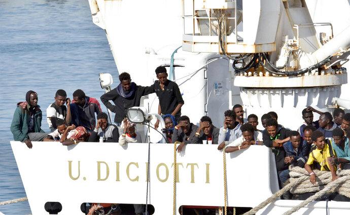 Migrants wait to disembark from an Italian Coast Guard vessell