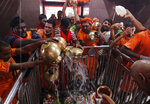 Indian Hindu Kanwarias, worshippers of the Hindu God Shiva, offer holy water from the Ganges River at Padilla Mahadev temple, on the outskirts of Prayagraj, India, Sunday, Sept. 27, 2020. Kanwarias are devotees performing a ritual pilgrimage in which they walk the roads of India, clad in saffron, and carry ornately decorated canisters of the sacred water from the Ganges River to take back to Hindu temples in their hometowns. (AP Photo/Rajesh Kumar Singh)
