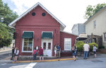 Passersby gather to take photos in front of the Red Hen Restaurant, Saturday, June 23, 2018, in Lexington, Va. White House press secretary Sarah Huckabee Sanders said Saturday in a tweet that she was booted from the Virginia restaurant because she works for President Donald Trump. Sanders said she was told by the owner of The Red Hen that she had to