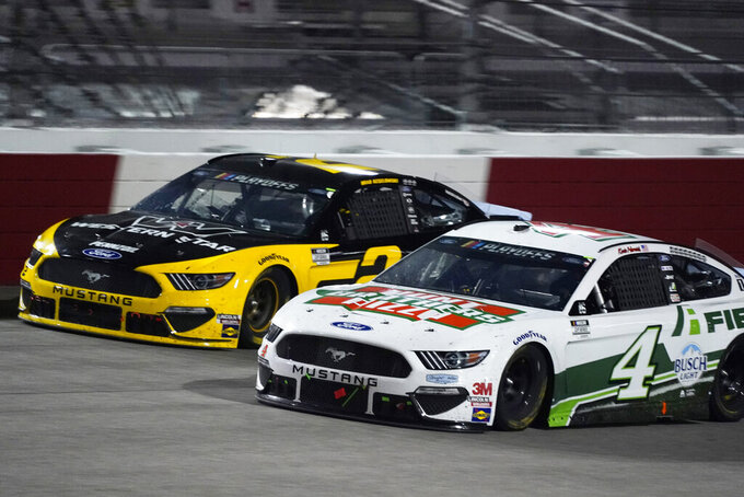 Brad Keselowski (2) and Kevin Harvick (4) drive into turn one during a NASCAR Cup Series auto race Saturday, Sept. 12, 2020, in Richmond, Va. (AP Photo/Steve Helber)