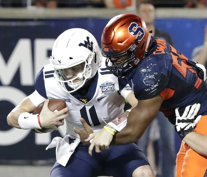 West Virginia quarterback Jack Allison (11) is sacked by Syracuse defensive lineman Kendall Coleman, right, during the second half of the Camping World Bowl NCAA college football game Friday, Dec. 28, 2018, in Orlando, Fla. (AP Photo/John Raoux)
