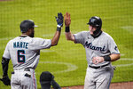 Miami Marlins' Chad Wallach celebrates with Starling Marte (6) after scoring on a Jon Berti double during the sixth inning of a baseball game against the Atlanta Braves on Thursday, Sept. 24, 2020, in Atlanta. (AP Photo/John Bazemore)